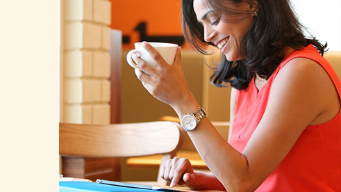 A woman smiling and holiding a cup while looking at her tablet